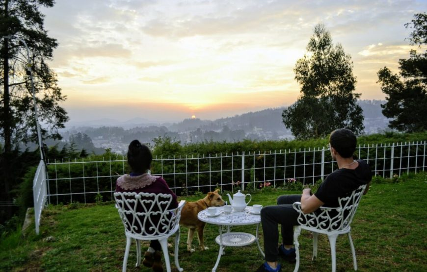 A couple is sitting and viewing sunrise in one of Chess playing table of the luxury resorts in ooty