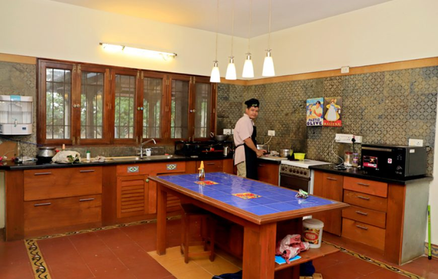 A person is cooking in the farm house stay in Bangalore